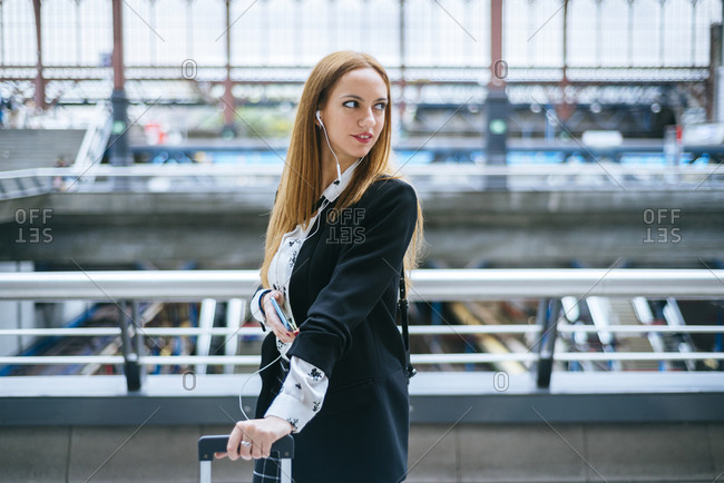 Young woman with earphones and cell phone turning round at train station