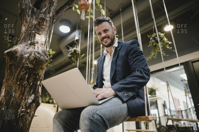 Businessman using laptop in coworking space- sitting on swing