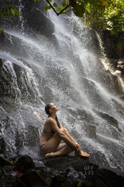 Young woman near Kanto Lampo waterfall- Bali- Indonesia