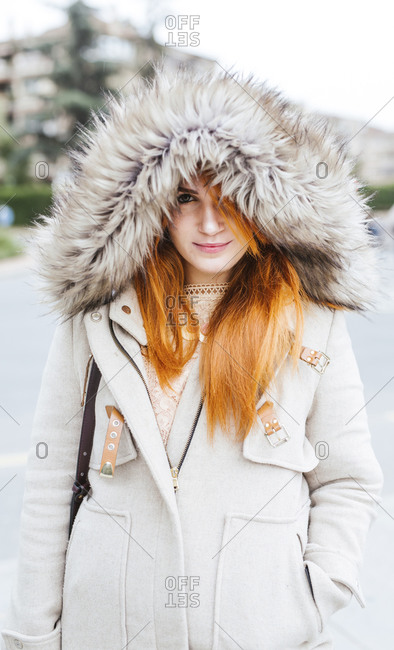 Portrait of young woman with orange dyed hair wearing hooded jacket in autumn