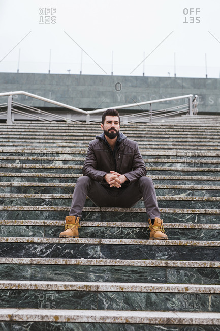 Portrait of bearded man sitting on stairs outdoors