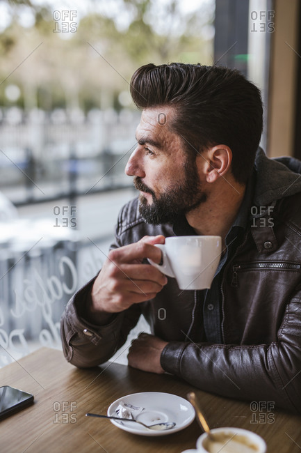 Bearded mature man in a coffee shop looking out of window