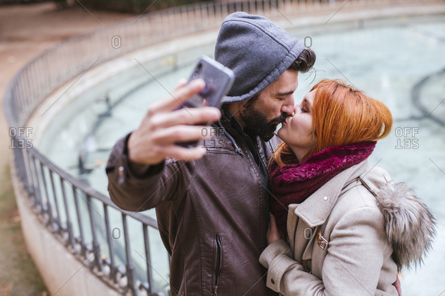 Kissing couple taking selfie with smartphone