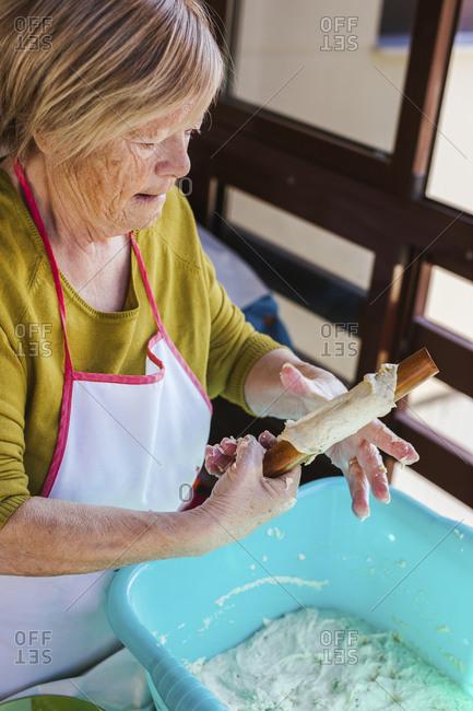 Senior woman preparing Spanish Christmas pastry Pestinos