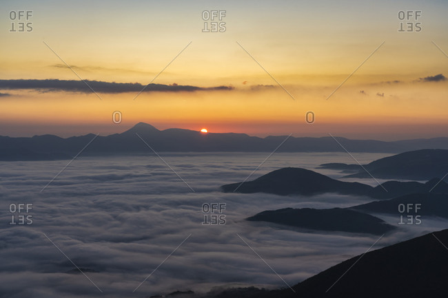 Italy- Thick fog shrouding Monte San Vicino at autumn sunrise