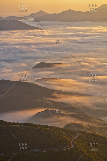 Italy- Aerial view of thick morning fog shrouding forested valley in Apennine Mountains