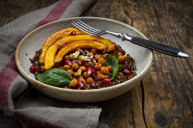 Bowl of quinoa with baked pumpkin- chick-peas- pomegranate- basil- walnuts and pumpkin seeds