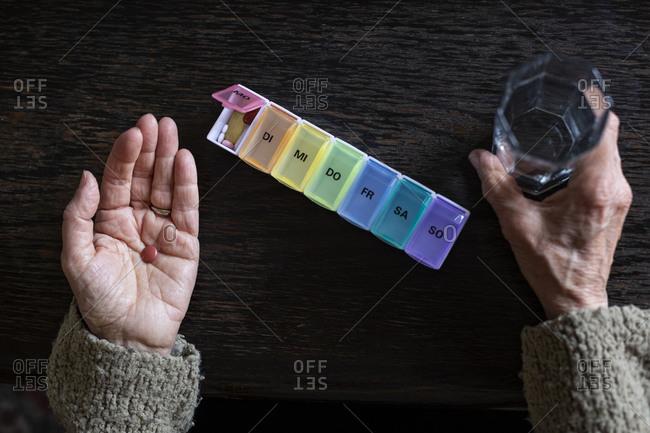 Senior woman taking medicine- water glass and pill organizer