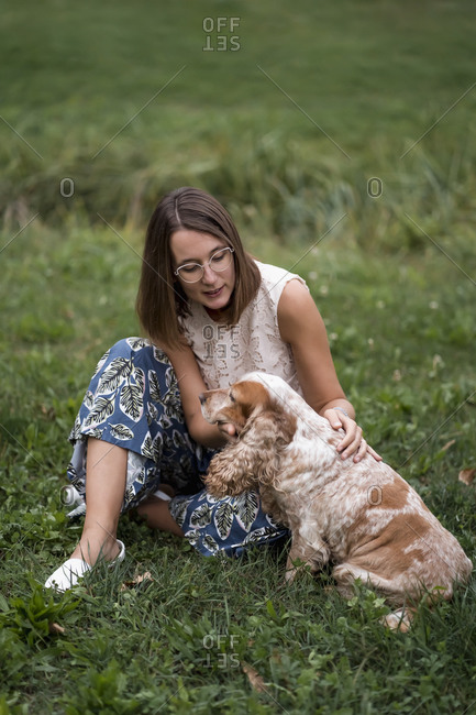 Woman sitting on a meadow with her dog