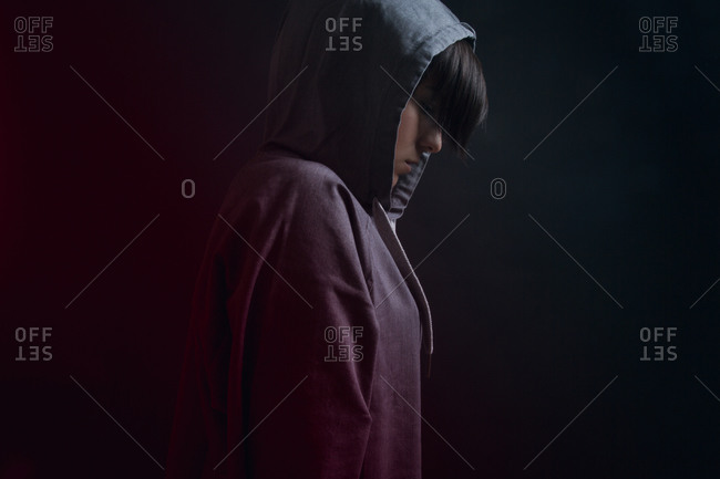 Side view of pensive youthful female in gray kangaroo wearing hood and standing on black background
