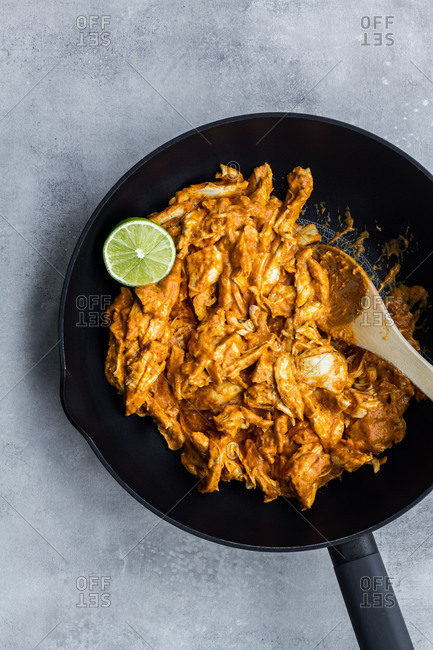 Top view of tasty spicy traditional chicken curry with lime in black pan with wooden spoon on grey stone background
