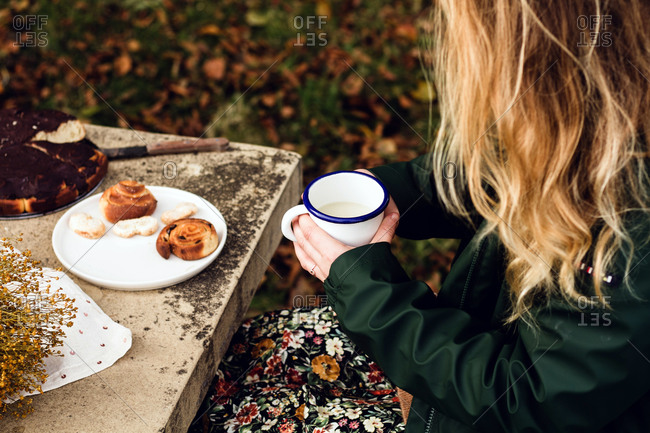 From above crop female in warm casual clothes drinking milk and eating delicious homemade pastry while sitting at gray stone table with bouquet of fresh yellow wildflowers in autumn garden