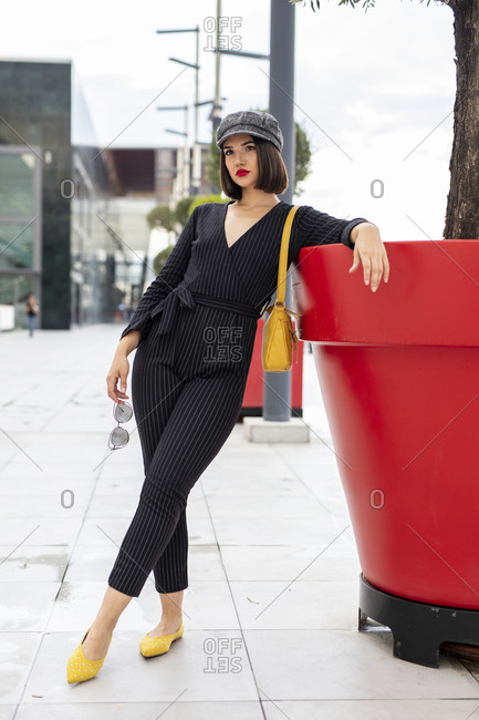Young black haired woman in trendy black combination and stylish accessories standing with crossed legs and looking away while leaning on red ornamental pot with tree at city street