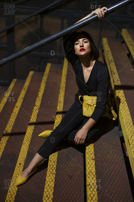 Fashionable woman in black dress with red lipstick and yellow small bag sitting at staircase handrail in a city street on dusk