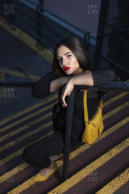 Fashionable woman in black dress with red lipstick and yellow small bag getting into peaky cap leaning at staircase handrail in a city street on dusk