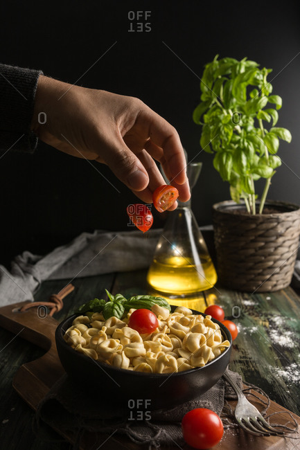 Crop hand of man throwing cut fresh cherry tomato on black ceramic bowl with homemade ravioli placed on cutting board on table with glass jar with olive oil and basil plant