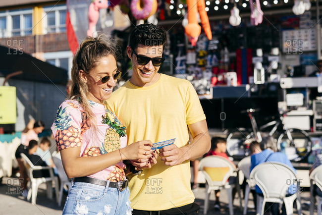 Excited woman in sunglasses and casual clothes looking at lottery ticket with handsome man enjoying time on fairground