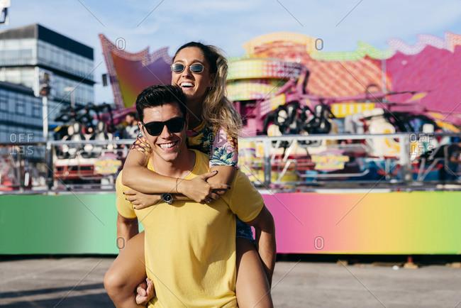 Positive lady riding on back of boyfriend