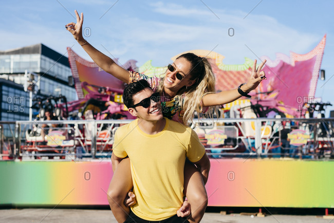 Glad female in sun glasses and casual clothes showing victory sign riding on back of handsome cheerful guy enjoying time in amusement park