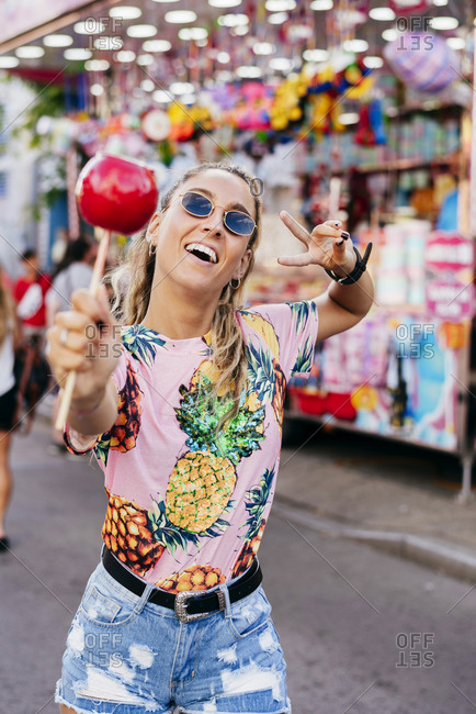 Bright smiling female in casual wear and sun glasses showing victory sign eating glazed apple spending time on fair