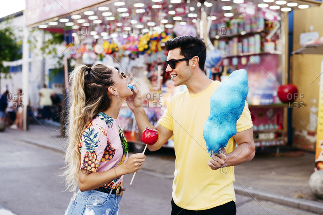 Happy male in sun glasses and casual clothes feeding young female with blue cotton candy while having fun on city fair
