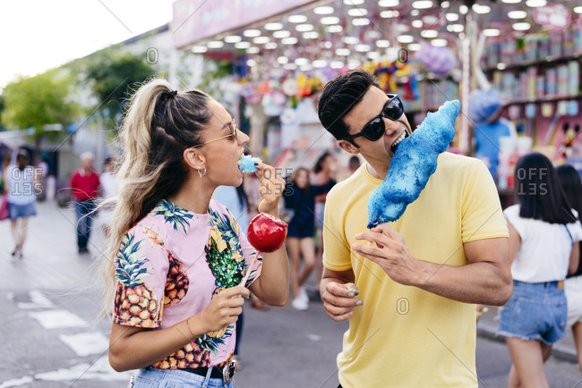 Satisfied man feeding girlfriend with cotton candy