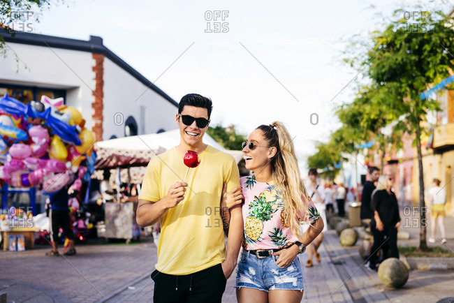 Content couple having fun walking on street in fair