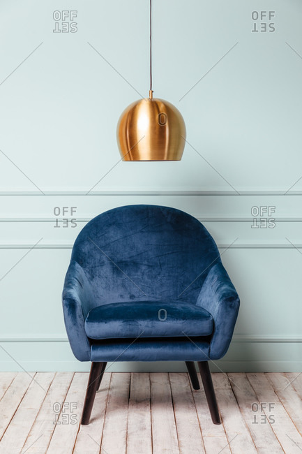 Blue armchair on turquoise background with a golden lamp