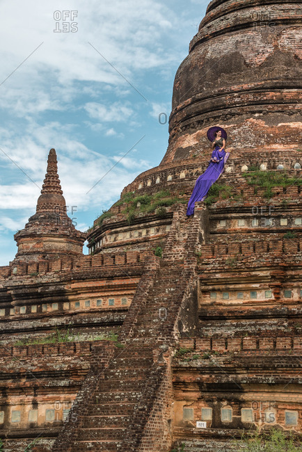 Woman standing on stairs of ancient buddhist temple