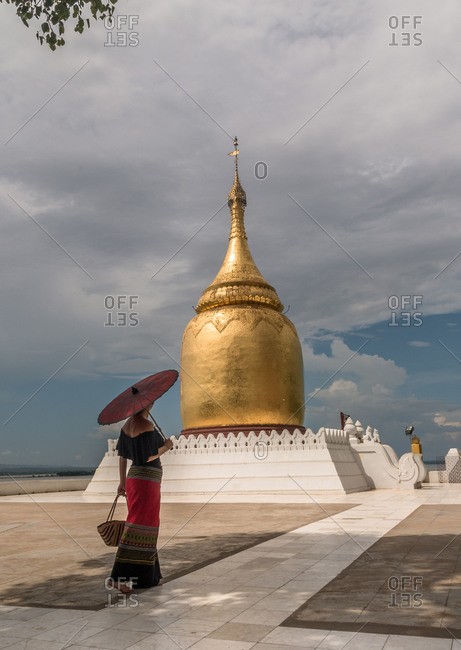 Back view of female in traditional long dress holding red umbrella and bag walking next to beautiful golden bell shaped burmese stupa in bagan myanmar