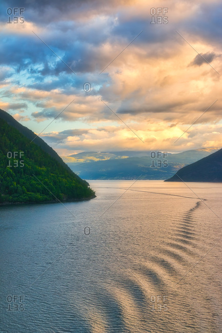 Great amazing landscape of sunlight through cloudy sky on wavy water between rocky mountains in norway
