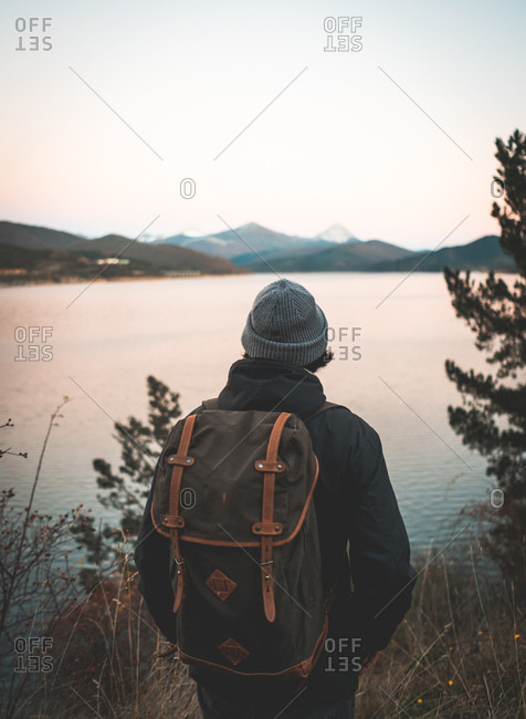 Back view of man in hat and warm jacket with backpack enjoying dark water reflecting sky and rocky snowy mountains around shore