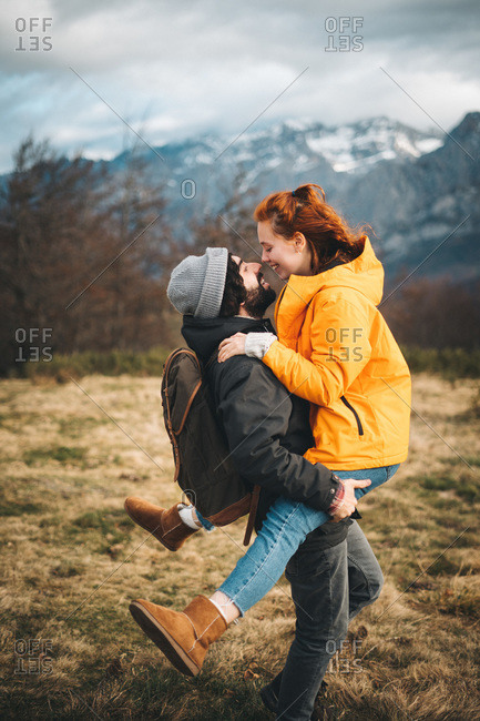 Side view of amorous man with backpack holding smiling woman on hand embracing and having fun in filed with dry grass near by mountains in cloudy day