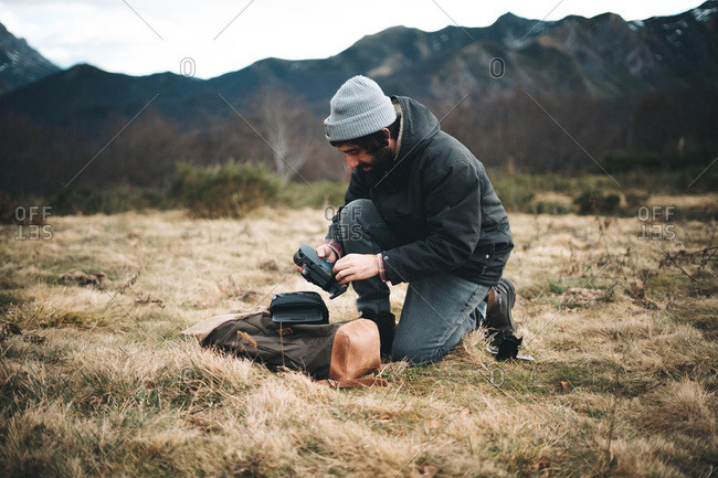 Side view of man in hat and warm jacket taking accessories from camera in meadow with dry grass