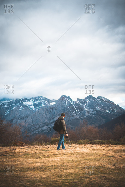 Back view of traveler in jacket with backpack and camera walking to  snowing mountain enjoying sightseeing