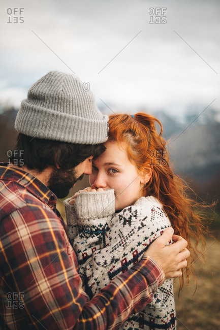 Side view of tender couple hugging and bonding with man closed eyes and woman looking at camera in cold day in mountains