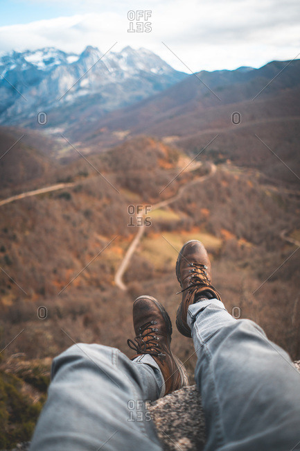 Crop traveler in brown boots sitting with legs dangling on edge on rock and enjoying breathtaking view of forest and road