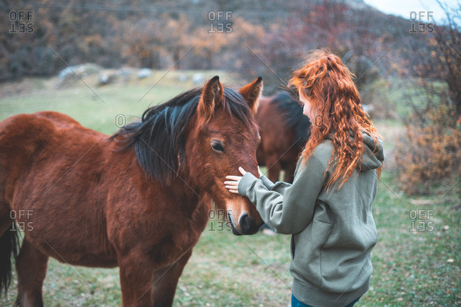 Back view of smiling woman with long red hair in hoodie stroking brown horse with black mane in mountain pasture
