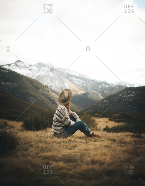 Side view of unrecognizable pensive charming woman with red hair in warm sweater sitting on lawn in mountain in gray day