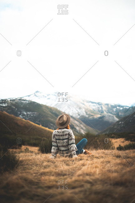 Back view of unrecognizable pensive charming woman with red hair in warm sweater sitting on lawn in mountain in gray day