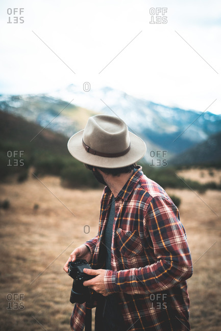 Stylish traveler in hat and shirt with photo camera looking back on stony mountains with tree