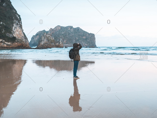 Side view of traveler in jacket with backpack taking photography on seaside surrounded with mountain
