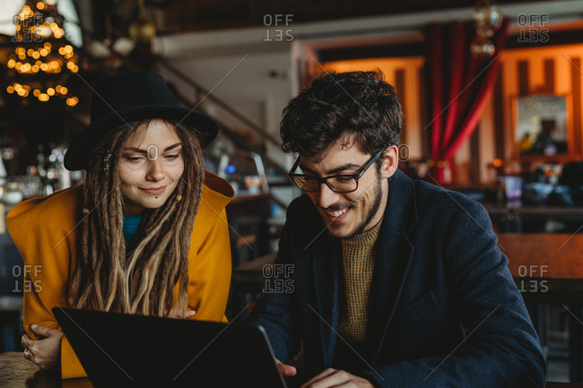 Smart man in glasses and stylish woman in hat looking at monitor while man typing on laptop in cafe