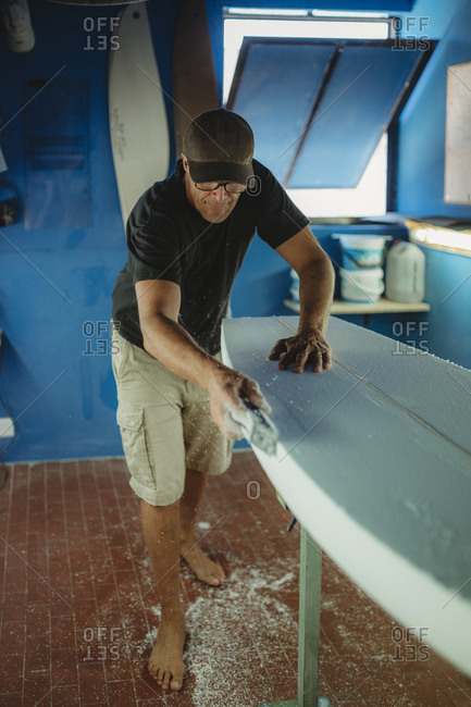 Woodworker diligently skinning surfboard in workshop