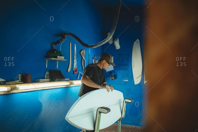 Carpenter diligently making surfboard in workshop