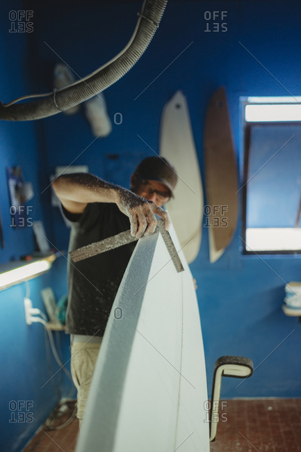 Qualified worker in uniform handling white surfboard in workshop with blue walls