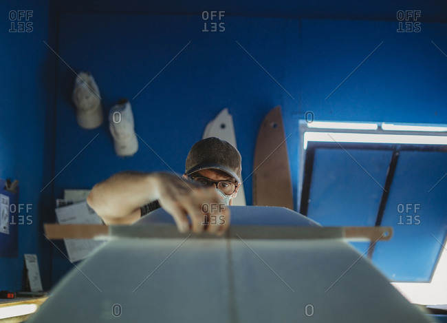 Concentrated qualified worker in protective mask aligning white surfboard in workshop with blue walls