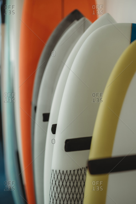 Variety of colorful surf and puddle boards arranged in row along wall and separated with black partitions