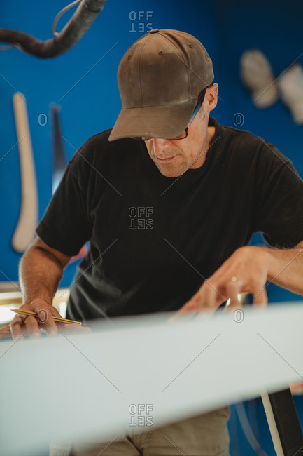 Craftsman making surf board in workshop
