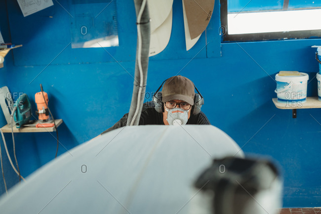 Craftsman in protective mask and headphones making surf board in small workshop with blue walls